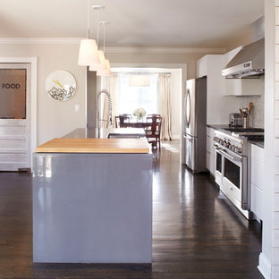 Inspiration for a mid-sized contemporary galley dark wood floor eat-in kitchen remodel in Atlanta with a farmhouse sink, flat-panel cabinets, white cabinets, gray backsplash, glass tile backsplash, stainless steel appliances and an island