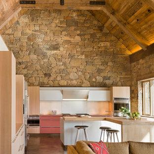 Modelo de cocina en L, rústica, abierta, con armarios con paneles lisos, puertas de armario de madera clara, encimera de madera, salpicadero blanco, salpicadero de vidrio templado y electrodomésticos de acero inoxidable