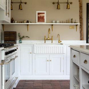 Modelo de cocina rústica con armarios estilo shaker, puertas de armario blancas, encimera de mármol, suelo de baldosas de terracota, una isla, suelo rojo y encimeras blancas