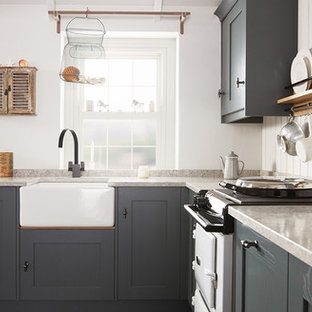 Design ideas for a mid-sized beach style l-shaped eat-in kitchen in Dublin with a farmhouse sink, shaker cabinets, distressed cabinets, solid surface benchtops, white appliances, ceramic floors, no island and timber splashback.
