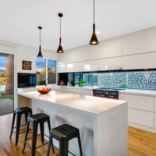 Offene, Große Moderne Küche in L-Form mit Landhausspüle, flächenbündigen Schrankfronten, weißen Schränken, Rückwand-Fenster, bunten Elektrogeräten, hellem Holzboden, Kücheninsel, beigem Boden, Quarzwerkstein-Arbeitsplatte, Küchenrückwand in Schwarz und grauer Arbeitsplatte in Melbourne