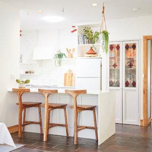 Réalisation d'une petite cuisine ouverte parallèle ethnique avec un évier de ferme, un placard à porte shaker, des portes de placard grises, un plan de travail en quartz modifié, une crédence blanche, une crédence en brique, un électroménager blanc, un sol en ardoise, une péninsule et un sol multicolore.