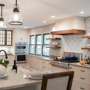 Zweizeilige, Große Landhausstil Wohnküche mit Landhausspüle, Kassettenfronten, weißen Schränken, Quarzwerkstein-Arbeitsplatte, Küchenrückwand in Blau, Rückwand aus Terrakottafliesen, Küchengeräten aus Edelstahl, braunem Holzboden, Kücheninsel, braunem Boden und grauer Arbeitsplatte in Minneapolis
