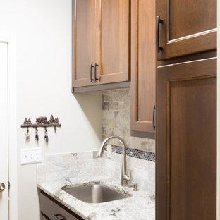 他の地域の中くらいのモダンスタイルのおしゃれなダイニングキッチン (アンダーカウンターシンク、フラットパネル扉のキャビネット、茶色いキャビネット、御影石カウンター、グレーのキッチンパネル、トラバーチンのキッチンパネル、シルバーの調理設備、無垢フローリング、茶色い床、グレーのキッチンカウンター) の写真