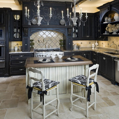 Example of a classic u-shaped travertine floor kitchen design in Dallas with paneled appliances, granite countertops, raised-panel cabinets, black cabinets and beige backsplash