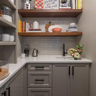 Klassische Küche in L-Form mit Vorratsschrank, Unterbauwaschbecken, Schrankfronten mit vertiefter Füllung, grauen Schränken, Küchenrückwand in Grau, Rückwand aus Glasfliesen, braunem Boden, weißer Arbeitsplatte und braunem Holzboden in Raleigh