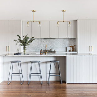Scandinavian galley kitchen in Sydney with a farmhouse sink, flat-panel cabinets, white cabinets, grey splashback, panelled appliances, medium hardwood floors, with island, brown floor and grey benchtop.