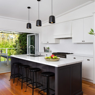 Design ideas for a transitional galley kitchen in Sydney with shaker cabinets, white cabinets, white splashback, black appliances, medium hardwood floors, with island, brown floor and white benchtop.