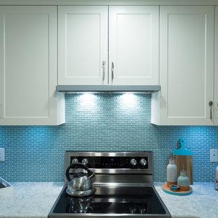 バンクーバーの小さいエクレクティックスタイルのおしゃれなキッチン (アンダーカウンターシンク、シェーカースタイル扉のキャビネット、白いキャビネット、クオーツストーンカウンター、青いキッチンパネル、モザイクタイルのキッチンパネル、シルバーの調理設備の) の写真