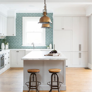 Transitional l-shaped kitchen in Sydney with a farmhouse sink, shaker cabinets, white cabinets, blue splashback, subway tile splashback, panelled appliances, medium hardwood floors, with island and brown floor.