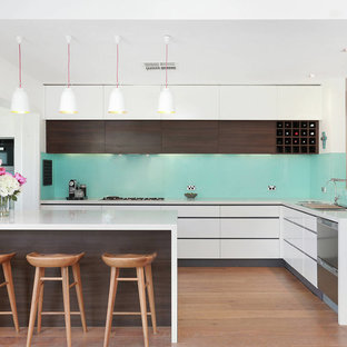 This is an example of a large contemporary l-shaped kitchen in Sydney with stainless steel appliances, white benchtop, a drop-in sink, flat-panel cabinets, white cabinets, blue splashback, medium hardwood floors, a peninsula and brown floor.