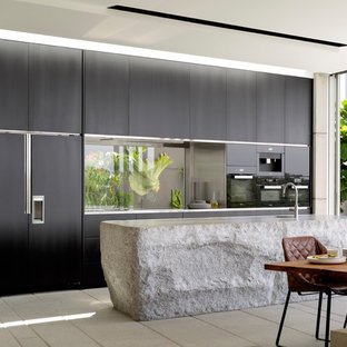 This is an example of a contemporary galley eat-in kitchen in Sydney with an undermount sink, flat-panel cabinets, black cabinets, glass sheet splashback, black appliances, with island and beige floor.