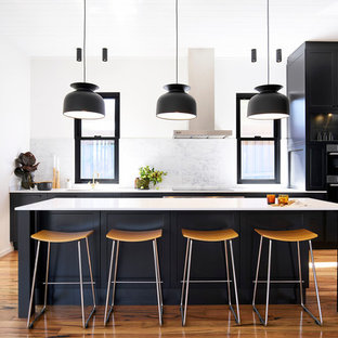 This is an example of a mid-sized transitional single-wall kitchen in Sydney with black cabinets, white splashback, marble splashback, stainless steel appliances, light hardwood floors, with island, brown floor and recessed-panel cabinets.