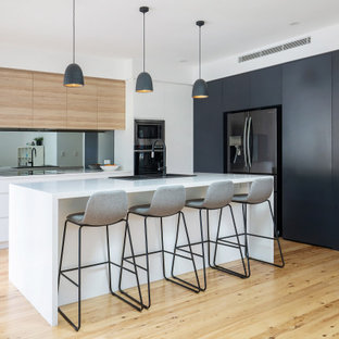 Mid-sized contemporary l-shaped open plan kitchen in Sydney with a drop-in sink, flat-panel cabinets, quartz benchtops, metallic splashback, mirror splashback, light hardwood floors, with island, white benchtop, black appliances and beige floor.