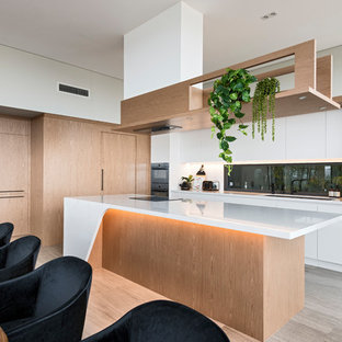 Inspiration for a large modern l-shaped eat-in kitchen in Perth with an undermount sink, light wood cabinets, solid surface benchtops, black appliances, porcelain floors, with island, grey floor, white benchtop, flat-panel cabinets and window splashback.