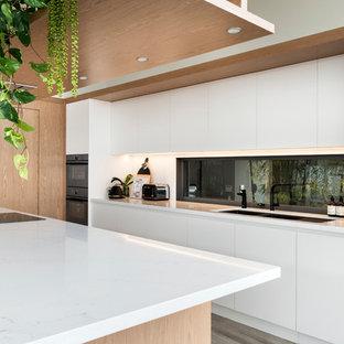 На фото: большая угловая кухня в стиле модернизм с обеденным столом, врезной раковиной, фасадами с утопленной филенкой, светлыми деревянными фасадами, столешницей из акрилового камня, белым фартуком, фартуком из каменной плиты, черной техникой, полом из керамогранита, островом, серым полом и белой столешницей