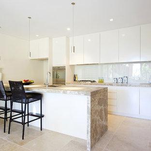 Diseño de cocina de galera, contemporánea, con armarios con paneles lisos, puertas de armario blancas, salpicadero blanco y salpicadero de vidrio templado