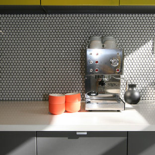 Mid-sized mid-century modern eat-in kitchen ideas - Example of a mid-sized 1950s galley terrazzo floor eat-in kitchen design in Baltimore with flat-panel cabinets, an island, ceramic backsplash, yellow cabinets, solid surface countertops, white backsplash, stainless steel appliances and an undermount sink
