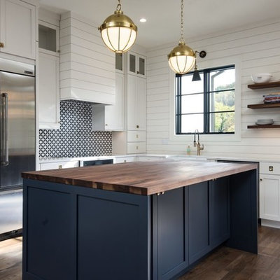 Inspiration for a mid-sized farmhouse l-shaped brown floor and dark wood floor kitchen remodel in Other with a farmhouse sink, white cabinets, stainless steel appliances, an island, shaker cabinets, wood countertops and multicolored backsplash