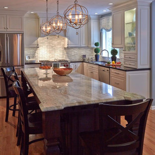 Design ideas for a large traditional u-shaped eat-in kitchen in Boston with a single-bowl sink, raised-panel cabinets, white cabinets, granite benchtops, white splashback, glass tile splashback, stainless steel appliances and with island.