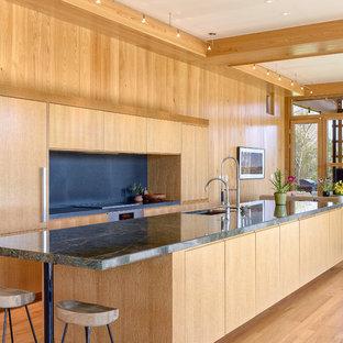 他の地域の大きいコンテンポラリースタイルのおしゃれなキッチン (アンダーカウンターシンク、フラットパネル扉のキャビネット、淡色木目調キャビネット、御影石カウンター、黒いキッチンパネル、スレートの床、パネルと同色の調理設備、緑のキッチンカウンター、無垢フローリング、茶色い床) の写真