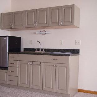 Неиссякаемый источник вдохновения для домашнего уюта: маленькая линейная кухня в классическом стиле с обеденным столом, накладной раковиной, фасадами с выступающей филенкой, серыми фасадами, столешницей из ламината, техникой из нержавеющей стали и ковровым покрытием