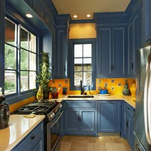 ダラスのトラディショナルスタイルのおしゃれなII型キッチン (アンダーカウンターシンク、フラットパネル扉のキャビネット、青いキャビネット、黄色いキッチンパネル、シルバーの調理設備の、トラバーチンの床、クオーツストーンカウンター、サブウェイタイルのキッチンパネル) の写真