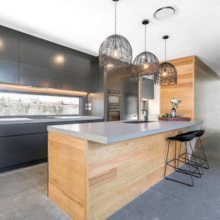 Photo of a mid-sized contemporary galley eat-in kitchen in Brisbane with a drop-in sink, flat-panel cabinets, black cabinets, mirror splashback, black appliances, concrete floors, multiple islands and grey floor.
