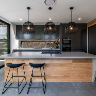 Contemporary galley kitchen in Brisbane with an undermount sink, flat-panel cabinets, black cabinets, concrete benchtops, window splashback, black appliances, concrete floors, with island, grey floor and grey benchtop.
