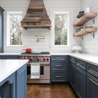 This is an example of a medium sized nautical l-shaped kitchen/diner in Charleston with recessed-panel cabinets, blue cabinets, marble worktops, white splashback, wood splashback, an island, brown floors, white worktops, stainless steel appliances and dark hardwood flooring.