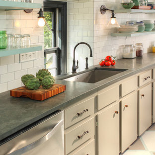 Photo of a large country single-wall kitchen in Richmond with an undermount sink, flat-panel cabinets, beige cabinets, zinc benchtops, white splashback, subway tile splashback, ceramic floors and beige floor.