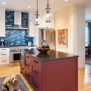 シアトルの中くらいのトランジショナルスタイルのおしゃれなキッチン (アンダーカウンターシンク、シェーカースタイル扉のキャビネット、白いキャビネット、クオーツストーンカウンター、青いキッチンパネル、磁器タイルのキッチンパネル、シルバーの調理設備、淡色無垢フローリング、黄色い床、茶色いキッチンカウンター) の写真