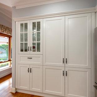 パースの中くらいのトラディショナルスタイルのおしゃれなキッチン (ドロップインシンク、落し込みパネル扉のキャビネット、白いキャビネット、御影石カウンター、白いキッチンパネル、磁器タイルのキッチンパネル、黒い調理設備、淡色無垢フローリング、黄色い床、黒いキッチンカウンター) の写真