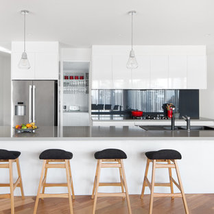 Design ideas for a contemporary galley kitchen in Melbourne with a drop-in sink, flat-panel cabinets, white cabinets, black splashback, glass sheet splashback, stainless steel appliances, medium hardwood floors, with island, brown floor and grey benchtop.