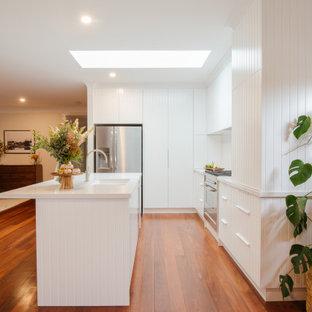 Стильный дизайн: угловая кухня среднего размера в современном стиле с двойной раковиной, фасадами с филенкой типа жалюзи, белыми фасадами, белым фартуком, техникой из нержавеющей стали, островом, оранжевым полом и белой столешницей - последний тренд
