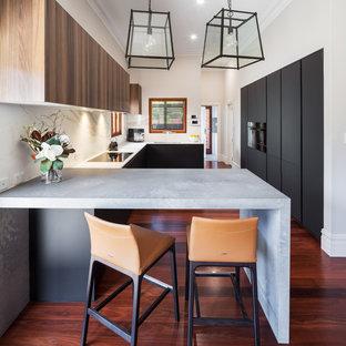 パースの広いコンテンポラリースタイルのおしゃれなコの字型キッチン (アンダーカウンターシンク、フラットパネル扉のキャビネット、黒いキャビネット、白いキッチンパネル、黒い調理設備、濃色無垢フローリング、赤い床、白いキッチンカウンター) の写真