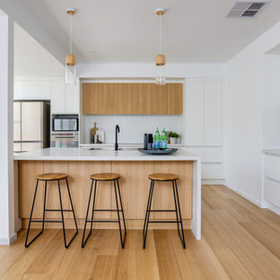 Inspiration for a large scandinavian u-shaped kitchen pantry in Melbourne with an undermount sink, recessed-panel cabinets, white cabinets, quartz benchtops, grey splashback, porcelain splashback, stainless steel appliances, medium hardwood floors, with island and white benchtop.