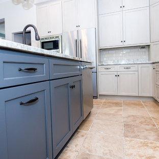 Foto di una cucina classica con lavello a vasca singola, ante in stile shaker, ante beige, top in granito, paraspruzzi beige, paraspruzzi con piastrelle diamantate, elettrodomestici in acciaio inossidabile, pavimento in gres porcellanato e isola