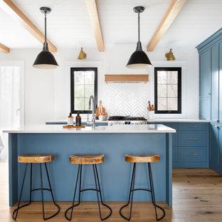モントリオールの中サイズのカントリー風おしゃれなキッチン (シェーカースタイル扉のキャビネット、青いキャビネット、クオーツストーンカウンター、白いキッチンパネル、シルバーの調理設備、白いキッチンカウンター、無垢フローリング) の写真