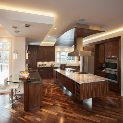 Inspiration for a contemporary brown floor kitchen remodel in Calgary with stainless steel appliances, flat-panel cabinets and dark wood cabinets