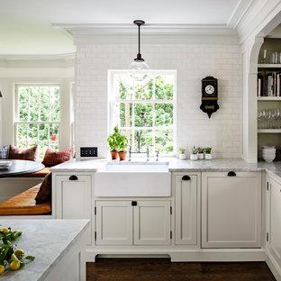 ポートランドのヴィクトリアン調のおしゃれなダイニングキッチン (エプロンフロントシンク、シェーカースタイル扉のキャビネット、白いキャビネット、白いキッチンパネル、サブウェイタイルのキッチンパネル、濃色無垢フローリング) の写真