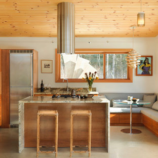 Inspiration for a small rustic l-shaped kitchen/diner in Burlington with shaker cabinets, medium wood cabinets, stainless steel appliances, an island, a submerged sink, granite worktops, beige floors and concrete flooring.
