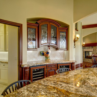 Photo of an expansive traditional u-shaped open plan kitchen in Denver with an undermount sink, louvered cabinets, medium wood cabinets, granite benchtops, white splashback, limestone splashback, stainless steel appliances, medium hardwood floors, with island and brown floor.