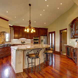 This is an example of an expansive traditional u-shaped open plan kitchen in Denver with an undermount sink, louvered cabinets, medium wood cabinets, granite benchtops, white splashback, limestone splashback, stainless steel appliances, medium hardwood floors, with island and brown floor.