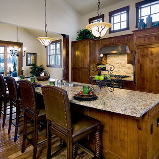 Large traditional eat-in kitchen pictures - Large elegant l-shaped medium tone wood floor eat-in kitchen photo in Seattle with a single-bowl sink, shaker cabinets, medium tone wood cabinets, limestone countertops, beige backsplash, stone tile backsplash, paneled appliances and an island