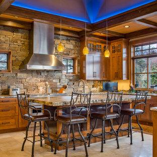 Cette image montre une cuisine chalet avec un placard à porte shaker, des portes de placard en bois brun, un îlot central, une crédence marron, une crédence en carrelage de pierre et un sol beige.