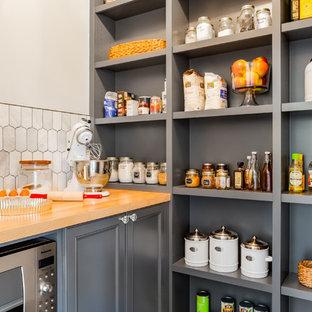 シアトルの中サイズのエクレクティックスタイルのおしゃれなキッチン (落し込みパネル扉のキャビネット、グレーのキャビネット、木材カウンター、白いキッチンパネル、大理石の床、シルバーの調理設備の、アイランドなし、茶色いキッチンカウンター) の写真
