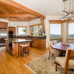 Foto de cocina minimalista, grande, abierta, con fregadero encastrado, armarios con paneles lisos, puertas de armario marrones, encimera de mármol, electrodomésticos de acero inoxidable, suelo de madera clara y una isla