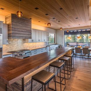 Modelo de cocina comedor rural con armarios estilo shaker, salpicadero multicolor, salpicadero de azulejos en listel, electrodomésticos de acero inoxidable, una isla y suelo de madera en tonos medios