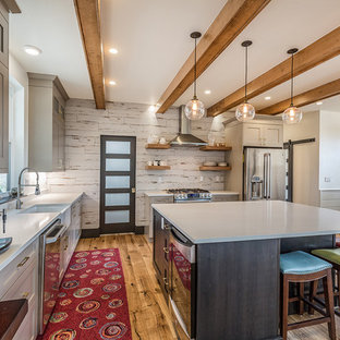 Cottage l-shaped medium tone wood floor and brown floor eat-in kitchen photo in Albuquerque with a farmhouse sink, shaker cabinets, gray cabinets, white backsplash, an island and gray countertops